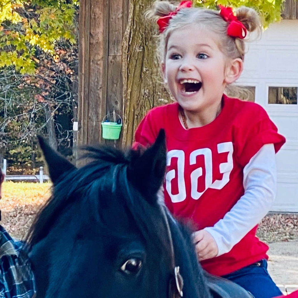 Excited little girl riding a horse at Flamig Farm
