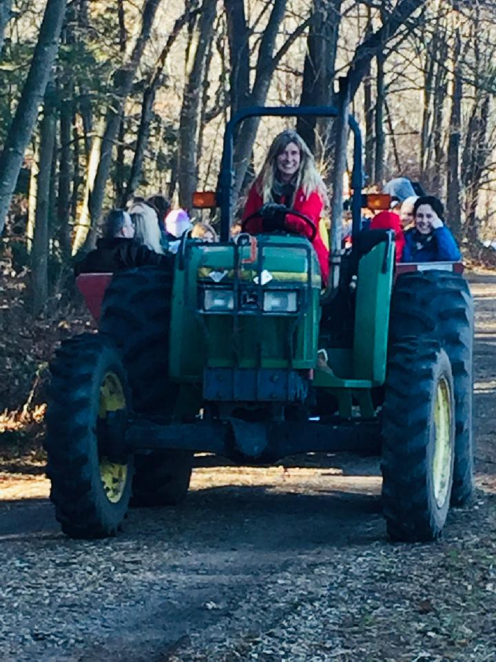 Farmer Julie smiling while driving a green tractor full of people